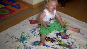 Αστείο παιδί μικρών παιδιών με τη χρωματισμένη ζωγραφική προσώπου στα ενδύματά του φιλμ μικρού μήκους