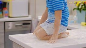 Αστείο παιχνίδι αγοριών στην κουζίνα με το αλεύρι ενοχλητικό παιδί στο hom Άτακτα παιδιά απόθεμα βίντεο