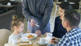 Αστείο παιχνίδι μικρών κοριτσιών με το παιχνίδι της πρίν τρώει το γεύμα της στον καφέ με τους γονείς της Ο σερβιτόρος της φέρνει  Στοκ φωτογραφία με δικαίωμα ελεύθερης χρήσης