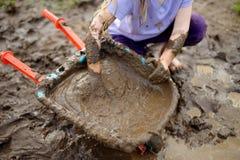 Αστείο παιχνίδι μικρών κοριτσιών σε μια μεγάλη υγρή λακκούβα λάσπης την ηλιόλουστη θερινή ημέρα Παιδί που παίρνει βρώμικο σκάβοντ Στοκ Εικόνες