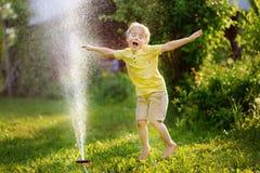 Αστείο παιχνίδι μικρών παιδιών με τον ψεκαστήρα κήπων στο ηλιόλουστο κατώφλι Στοκ Εικόνες