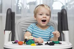 Αστείο παιχνίδι μικρών παιδιών χαμόγελου με τη ζύμη αργίλου ή διαμόρφωση Plasticine, έννοια εκπαίδευσης και φύλαξης Στοκ Εικόνες