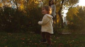 Αστείο παιχνίδι μωρών με το mom στο χορτοτάπητα τρεξίματα μωρών στο χορτοτάπητα κάτω από τη επίβλεψη της μητέρας του λίγο παιχνίδ απόθεμα βίντεο