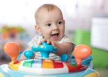 Αστείο παιχνίδι μωρών στον άλτη μωρών Στοκ Φωτογραφίες