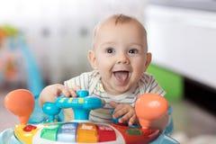 Αστείο παιχνίδι παιδιών στον περιπατητή μωρών Στοκ φωτογραφία με δικαίωμα ελεύθερης χρήσης