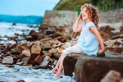 Αστείο παιχνίδι κοριτσιών παιδιών με τον παφλασμό νερού στην παραλία Ταξίδι στις θερινές διακοπές Στοκ Φωτογραφία