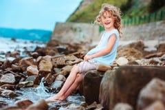 Αστείο παιχνίδι κοριτσιών παιδιών με τον παφλασμό νερού στην παραλία Ταξίδι στις θερινές διακοπές Στοκ Φωτογραφίες