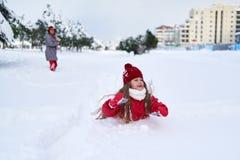 Αστείο παιχνίδι κοριτσιών τα φθινόπωρα χιονιού Στοκ εικόνα με δικαίωμα ελεύθερης χρήσης