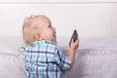 Αστείο παιχνίδι μικρών παιδιών με ένα τηλέφωνο εγχώριος πυροβολισμός Στοκ Εικόνα