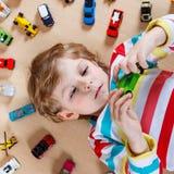 Αστείο παιχνίδι μικρών παιδιών με τα μέρη των αυτοκινήτων παιχνιδιών εσωτερικών Στοκ φωτογραφία με δικαίωμα ελεύθερης χρήσης