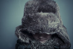 Αστείο παιδί με το καπέλο γουνών και το χειμερινό παλτό, την κρύες έννοια και τη θύελλα Στοκ Εικόνες