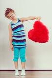 Αστείο παιδί μικρών κοριτσιών με το κόκκινο μαξιλάρι μορφής καρδιών Στοκ φωτογραφία με δικαίωμα ελεύθερης χρήσης