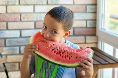 Αστείο παιδί που τρώει το καρπούζι στο εσωτερικό, εστίαση στα μάτια Στοκ Φωτογραφίες