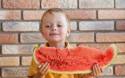 Αστείο παιδί που τρώει το καρπούζι στο εσωτερικό Στοκ φωτογραφία με δικαίωμα ελεύθερης χρήσης