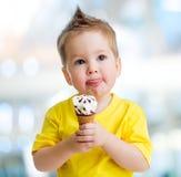 Αστείο παιδί που τρώει το παγωτό στο θολωμένο υπόβαθρο στοκ φωτογραφίες