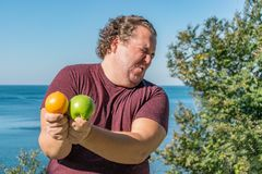 Αστείο παχύ άτομο στον ωκεανό που τρώει τα φρούτα Διακοπές, απώλεια βάρους και υγιής κατανάλωση στοκ φωτογραφία