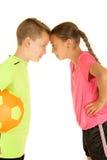 Αστείο πορτρέτο ενός αγοριού & ενός κοριτσιού στις στολές ποδοσφαίρου που κλίνουν να αγγίξει στοκ φωτογραφία με δικαίωμα ελεύθερης χρήσης