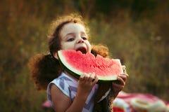 Αστείο πορτρέτο ενός απίστευτα όμορφου σγουρός-μαλλιαρού μικρού κοριτσιού που τρώει το καρπούζι, υγιές πρόχειρο φαγητό φρούτων, λ στοκ εικόνα