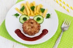 Αστείο πρόσωπο τροφίμων με μια μπριζόλα, τις τηγανιτές πατάτες και το αγγούρι Στοκ Εικόνες