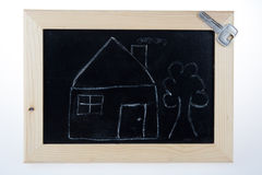 Αστείο σκίτσο του σπιτιού με το δέντρο και του κλειδιού στον πίνακα Στοκ Φωτογραφία