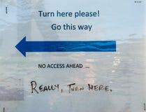 Αστείο σπιτικό κατευθυντικό οδικό σημάδι στροφής εδώ με το αριστερό που αντιμετωπίζει το μπλε βέλος στοκ φωτογραφία
