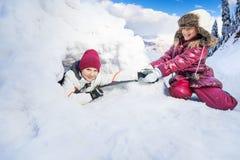 Αστείο τράβηγμα κοριτσιών στο φίλο της από την παγοκαλύβα χιονιού Στοκ Φωτογραφία