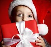 Αστείο χαμογελώντας παιδί στο κόκκινο δώρο Χριστουγέννων εκμετάλλευσης καπέλων Santa υπό εξέταση στοκ φωτογραφίες