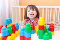 Αστείο χαμογελώντας μικρό παιδί που παίζει τους πλαστικούς φραγμούς Στοκ Φωτογραφία