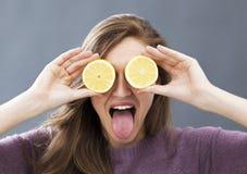 Αστείο όμορφο κορίτσι με τα zesty λεμόνια στα μάτια για το όραμα διασκέδασης στοκ εικόνες