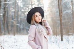 Αστείο όμορφο κορίτσι σε ένα καπέλο και παλτό στο υπόβαθρο WI Στοκ φωτογραφίες με δικαίωμα ελεύθερης χρήσης