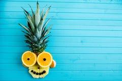 Αστείο applique από τα κομμάτια των φρούτων σε ένα μπλε ξύλινο υπόβαθρο Κεφάλι φρούτων φιαγμένο από ανανά, πορτοκάλι, διάστημα αν Στοκ Φωτογραφίες