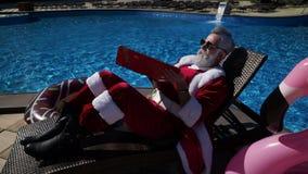 Αστείο Santa που χρησιμοποιεί το lap-top κάθεται στο μόνιππο και να αστειευτεί απόθεμα βίντεο