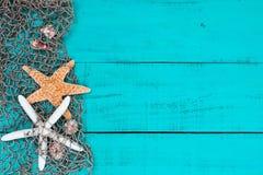 Αστερίας και κοχύλια στα ψάρια που πιάνουν στο μπλε ξύλινο σημάδι κιρκιριών Στοκ εικόνα με δικαίωμα ελεύθερης χρήσης