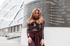Αστική Ευρωπαία αρκετά νέα γυναίκα στο εκλεκτής ποιότητας παντελόνι με ένα πορφυρό ακρωτήριο σε μια μοντέρνη μπλούζα με μια τοποθ στοκ φωτογραφία