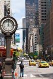 Αστική ζωή πόλεων της Νέας Υόρκης με τα taxis που περνά από τη 5η λεωφόρο και ένα μεγάλο ρολόι οδών. Στοκ εικόνα με δικαίωμα ελεύθερης χρήσης