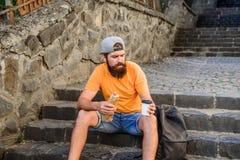 Αστικός τρόπος ζωής και ανθυγειινή διατροφή Το ξένοιαστο hipster τρώει το άχρηστο φαγητό ενώ καθίστε στα σκαλοπάτια Πεινασμένο πρ στοκ εικόνα με δικαίωμα ελεύθερης χρήσης