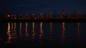 Αστικό τοπίο νύχτας με τα φω'τα πόλεων που απεικονίζονται στο νερό απόθεμα βίντεο
