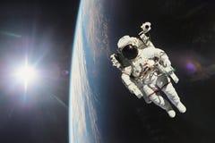 Αστροναύτης στο μακρινό διάστημα με το πλανήτη Γη ως σκηνικό στοιχεία Στοκ Εικόνα