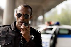 αστυνομικός αφροαμερικάνων που μιλά από walkie-talkie στοκ φωτογραφίες