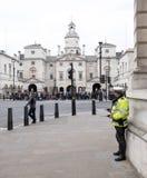 Αστυνομικός με τη φρουρά στάσεων ομιλουσών ταινιών walkie κοντά στις φρουρές αλόγων του λ Στοκ Εικόνες