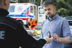 Αστυνομικός που εξετάζει την ηρεμία του φοβησμένου οδηγού στοκ φωτογραφία