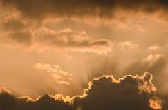 Ασυνήθιστες ακτίνες ήλιων ηλιοβασιλέματος που διαπερνούν μέσω των χνουδωτών σύννεφων στον πορτοκαλή ουρανό σε μια καυτή θερινή ημ Στοκ Εικόνες