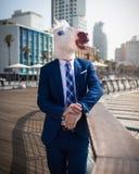 Ασυνήθιστος νεαρός άνδρας στις κομψές στάσεις κοστουμιών στην προκυμαία πόλεων στοκ φωτογραφίες