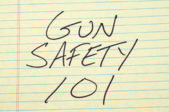 Ασφάλεια 101 πυροβόλων όπλων σε ένα κίτρινο νομικό μαξιλάρι Στοκ Εικόνα