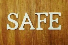 Ασφαλείς επιστολές αλφάβητου λέξης στο ξύλινο υπόβαθρο στοκ εικόνες