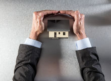 Ασφαλές σπίτι μόνωσης με τα χέρια επιχειρηματιών που προστατεύουν και που εξασφαλίζουν τη στέγη Στοκ εικόνα με δικαίωμα ελεύθερης χρήσης