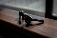Ασύρματα μαύρα earbuds σε μια ξύλινη σύσταση στοκ φωτογραφίες με δικαίωμα ελεύθερης χρήσης