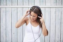 Ασύρματη μουσική ακούσματος γυναικών με τα ακουστικά από ένα έξυπνο τηλέφωνο Στοκ εικόνες με δικαίωμα ελεύθερης χρήσης