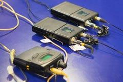 Ασύρματη συσκευή αποστολής σημάτων μικροφώνων τρία και ασύρματος δέκτης μικροφώνων τρία στον μπλε πίνακα στοκ εικόνα με δικαίωμα ελεύθερης χρήσης