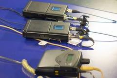 Ασύρματη συσκευή αποστολής σημάτων μικροφώνων τρία και ασύρματος δέκτης μικροφώνων τρία στον μπλε πίνακα στοκ φωτογραφία με δικαίωμα ελεύθερης χρήσης